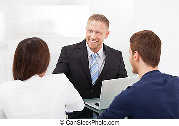 Financial Advisor Discussing With Couple - Smiling financial...