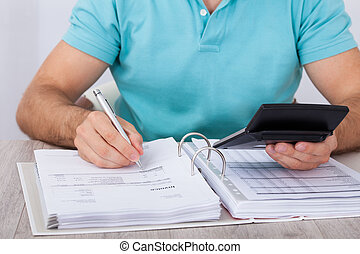 Man Calculating Financial Expenses - Midsection of man...