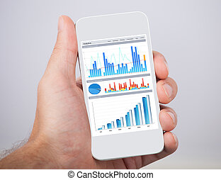 Hand Holding Mobile Phone With Financial Charts - Closeup of...