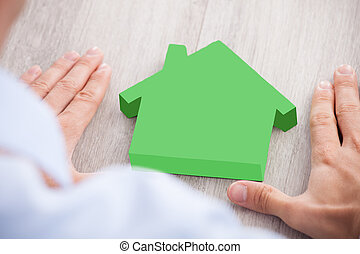Businessman Forming Hand Frame Around Green House Model