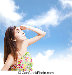 young woman raising hand to cover sunlight with blue sky