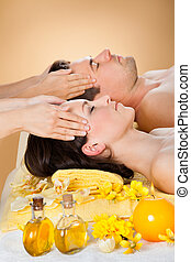 Relaxed Couple Receiving Head Massage At Spa - Side view of...