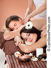 Couple Receiving Shoulder Massage At Spa - Portrait of young...