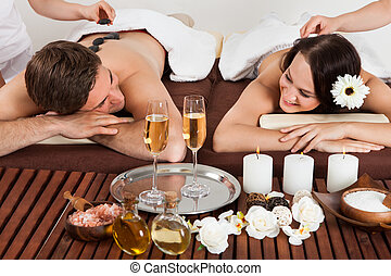 Couple Enjoying Hot Stone Massage At Spa - Smiling young...