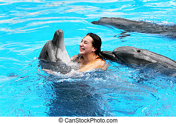 Happy beautiful young girl laughs and swims with dolphins in...