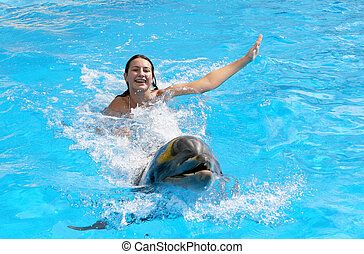 Beautiful young happy girl laughs and swims with dolphins in the blue dolphin pool lesson