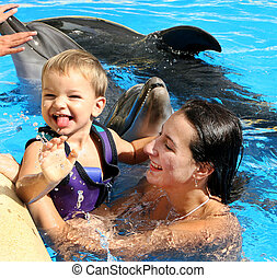 Happy beautiful young woman with a small child laughs and...