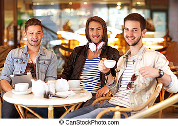 young hipster guys sitting in a cafe chatting and drinking...