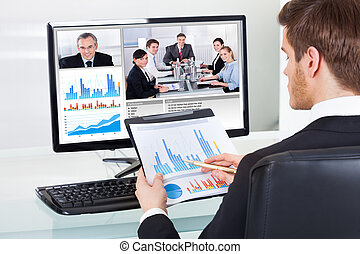 Businessman Video Conferencing With Colleagues - Young...