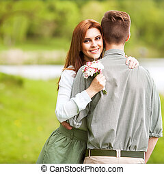 young happy couple sitting on river at sunset - young happy...