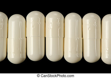 White Pills (Capsules) on Black Background - White pills...