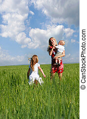 mother and two children in green field