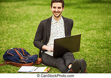 young fashion male student sitting on grass in park and...