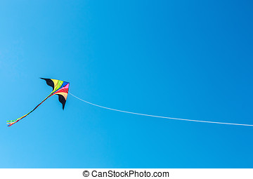 kite with tail in clear blue sky - Multicolored kite with...