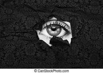stylish eye - Female eye peeking through a hole in black...