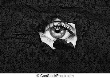 stylish eye - Female eye peeking through a hole in black...