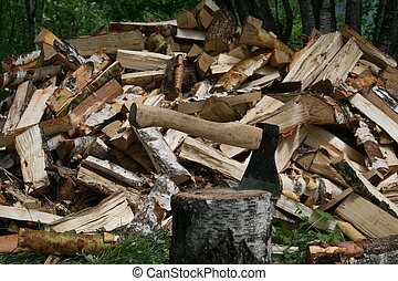 The axe and a pile of logs in the forest - The axe on the...