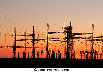 Power pylons - Silhouetted power pylons against a red sky at...