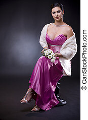 Woman in evening dress - Beautiful young woman sitting on a...