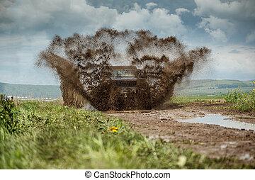 Off road car in muddy road splashing mud