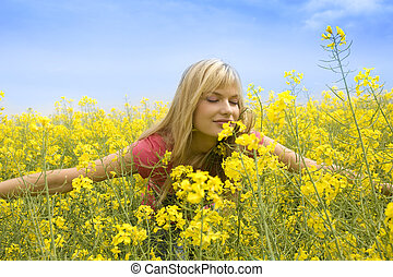 smelling yellow flowers - happy blond girl with open arms...
