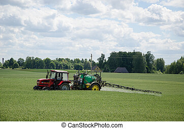 tractor spray green crop field in summer - tractor spraying...