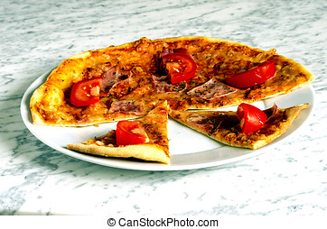 Homemade piza on a plate on a marble table