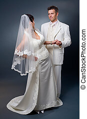 Bride and Groom posing in wedding dress at studio, looking...