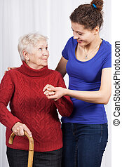 Young girl helping senior woman with a crutch