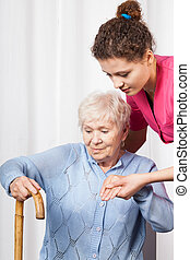 Nurse helping woman get up - Nurse helping elderly woman get...