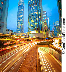City road tunnels light trails of modern landmark buildings...