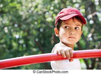 Portrait of a 3-4 years boy playing on the playground in...