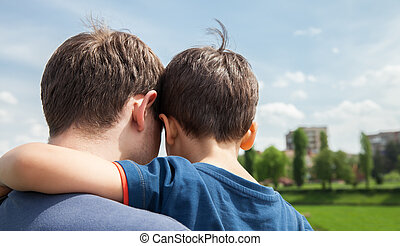Father and son on a city background View from the back