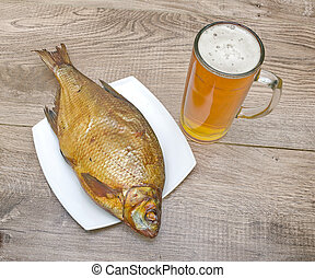 Smoked bream and a glass of beer on a wooden table -...