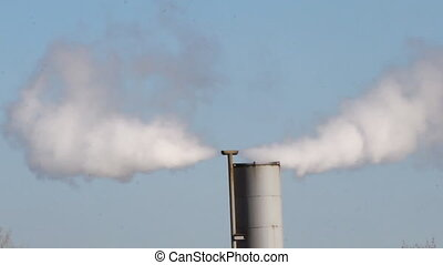 steam from a pipe at plant - streams of white steam take off...