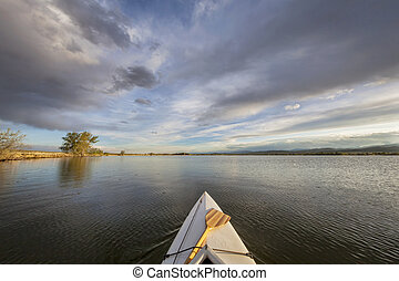 canoe with a paddle on lake - canoe bow with a paddle on a...