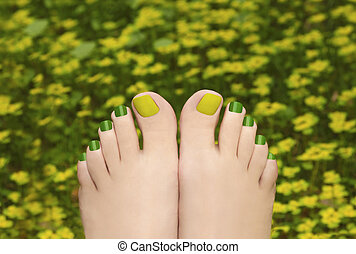 Pedicure in the grass. - Green with yellow pedicure female...