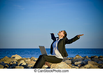 attractive business woman working on laptop at beach -...
