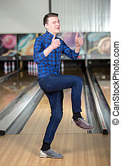 Bowling Game - Cheerful young man playing bowling
