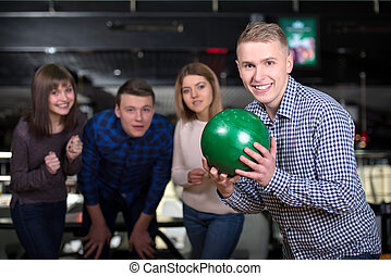 Bowling Game - Group of four friends in a bowling alley...