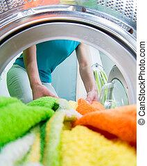 householder, mulher, carregando, roupa, lavando, máquina