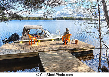 Lake pier with senior woman sitting on chair and looking far...