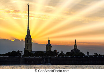 Silhouette of Peter and Paul Fortress with sunset and sun...