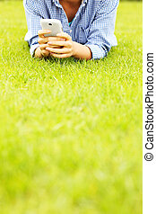 Woman with cellphone on grass