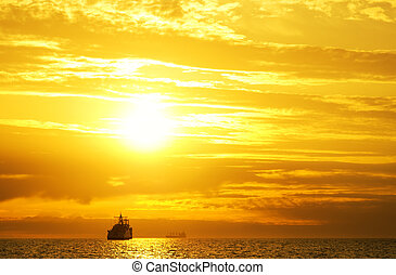 colorful sunset - Cargo ship sailing away against colorful...