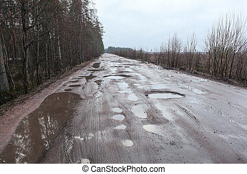 Broken asphalt road with holes and puddles
