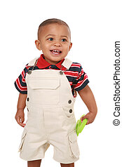 Smiling 1-year old baby boy standing holding toy on isolated...