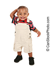 Smiling 1-year old baby boy standing facing camera on...