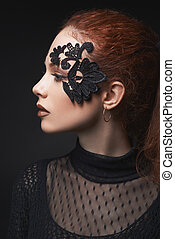 beautiful red-haired girl lace makeup in the dark background