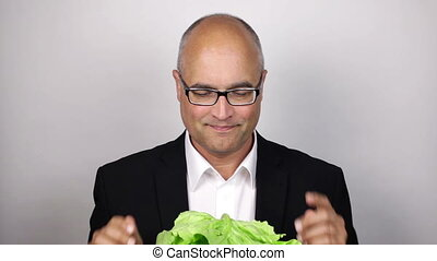 Eating salad - healthy lifestyle - Funny balding man eating...
